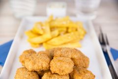 Fish nuggets with french fries Stock Images