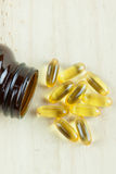 Fish Oil Arranged on wooden background with bottle laying down. Fish Oil Arranged on wooden background with bottle Stock Images