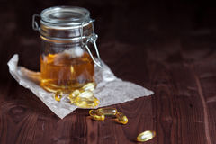 Fish oil, in Bank and capsules. On the table. Shallow depth of field, focus is on capsules Stock Photo