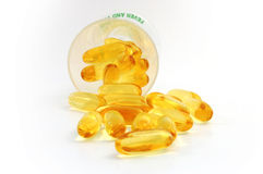 Fish oil caplets spilling out from the cup Royalty Free Stock Photo