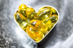 Fish oil capsule on heart shape box on black plate royalty free stock photos