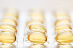 Fish oil capsules. Yellow gel capsules - close up Stock Photography