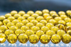 Fish oil capsules. Close up of golden colored oil capsules Stock Photos