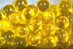 Fish oil capsules. Shiny yellow capsules with fish oil close-up image Royalty Free Stock Photo
