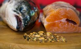 Fish oil capsules on the background of a salmon head and a piece of red fish,. Fish oil capsules on the background of a salmon head and a piece of red fish Stock Photos