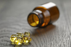 Fish oil capsules with bottle on wooden table Royalty Free Stock Photos