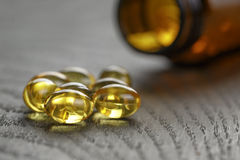 Fish oil capsules with bottle on wooden table Royalty Free Stock Images