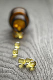 Fish oil capsules with bottle on wooden table Stock Photos