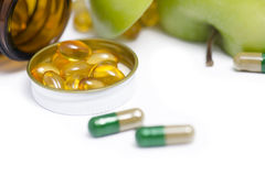 FISH OIL CAPSULES. On cap of medicine bottle on white background royalty free stock photography