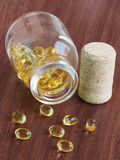 Fish oil capsules coming out of glass bottle on wooden backgroun Stock Photos
