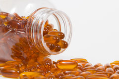 Fish oil capsules and container Stock Photography