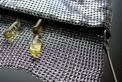 Fish Oil Capsules in Evening Bag. Three omega 3 fish oil capsules coming out of a fancy evening bag; they keep you going Royalty Free Stock Photography