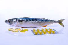 Fish oil capsules and fish mackerel (on white background). Fish oil capsules and fish mackerel on white background Stock Images