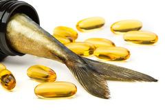 Fish oil capsules and fish tail in brown jar. Over white background Stock Image
