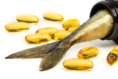 Fish oil capsules and fish tail in brown jar. Yellow fish oil capsules and fish tail in brown jar Royalty Free Stock Images