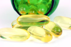 Fish oil capsules with green pill bottle Stock Images