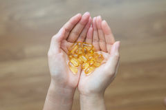 Fish Oil Capsules in Hand Stock Images