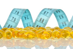 Fish oil capsules  and  measuring tape Royalty Free Stock Photography