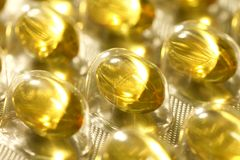 Fish oil capsules in packaging. Close up of capcules with fish oil in the tranculent plastic packaging Royalty Free Stock Photos