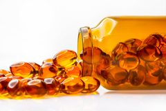 Fish oil capsules from the glass bottle on white background. Fish oil capsules are poured out from brown medical bottle contains unsaturated fatty acids stock image