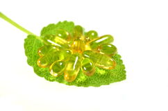 Fish oil capsules on sage leaf Stock Images