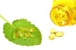 Fish oil capsules on sage leaf Stock Image