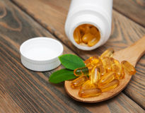 Fish oil capsules in a spoon. On a wooden background Royalty Free Stock Photos