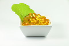 Fish oil capsules with vegetable leaf in cup Stock Images