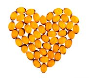 Fish oil capsules on white background. Oil capsules arranged in a hearth shape contains unsaturated fatty acids Stock Image