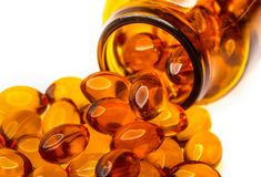 Fish oil capsules on white. Fish oil capsules are poured out from brown medical bottle contains unsaturated fatty acids stock photography
