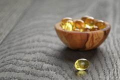 Fish oil capsules in wood bowl on wooden table Stock Photography