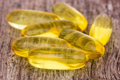Fish oil capsules on the wood Royalty Free Stock Photo