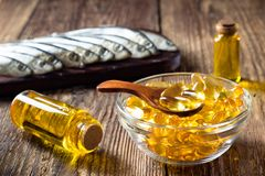 Fish oil capsules on wooden background royalty free stock photography