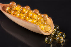 Fish oil capsules in a wooden scoop on a dark background Stock Photos