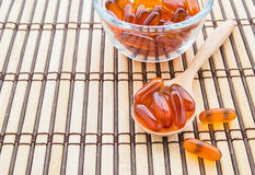 Fish oil capsules in wooden spoon on bamboo mat Royalty Free Stock Photography