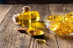 Fish oil capsules on wooden table, vitamin D supplement royalty free stock photo