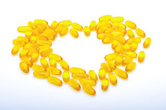 Fish oil capsules  yellow heart shaped. Fish oil capsules, vitamins yellow, heart shaped on white background Stock Photos