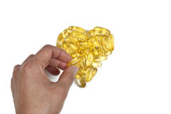 Fish oil heart. Fish oil capsules in heart shape. Hand putting last capsule in place Stock Photo