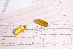 Fish oil for heart disease prevention. Fish oil pills put above an electrocardiogram Royalty Free Stock Image