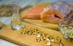 Fish oil is liquid and in capsules from salmon. Red salmon fish fresh on a wooden cutting board. Oil of omega 3 and omega 6 Royalty Free Stock Images