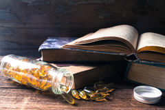 Fish oil and old books on the wooden background Stock Images