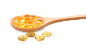 Fish oil pill in wooden spoon isolated on white Stock Photos