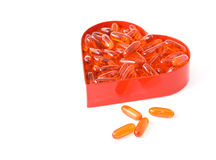 Fish oil pills in red heart shaped box. Isolated Royalty Free Stock Photo