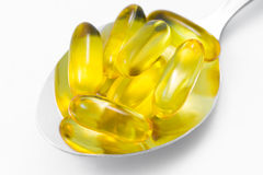 Fish Oil pills on serving spoon Royalty Free Stock Photos