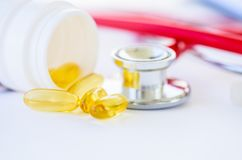 Fish oil pills with stethoscope on white background. Medical and health care concept Stock Photography