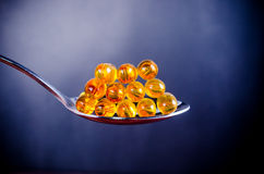 Fish oil on silver spoon Stock Photos