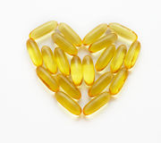 Fish oil supplements in a shape of a heart Stock Photos
