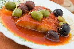 Fish with olives in tomato sauce. Royalty Free Stock Photo