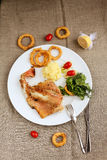 Fish with onion rings and rosemarry. Delicious fresh meal with baked fish and onion rings served with some mashed potatoes, cherry tomatoes, lemon and a Stock Photos