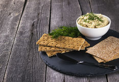 Fish pate with crackers against a dark background Royalty Free Stock Image